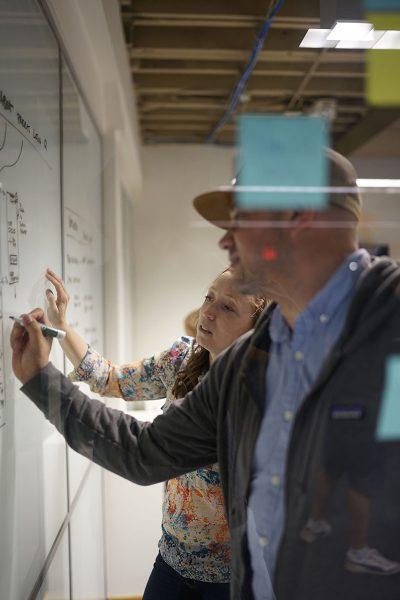 REGROUP team members writing on whiteboard